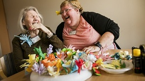 Elderly recipient of Day and respite care enjoying a conversation with carer