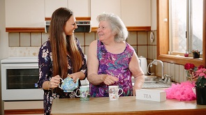 Thumbnail of elderly lady in discussion with care provider at kitchen worktop.