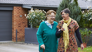 Two ladies leaving a suburban house, beginning a walk