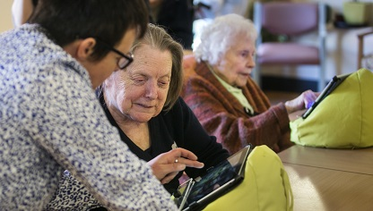 Image of clients receiving help with iPads