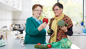 Two ladies examining recently purchased groceries on a kitchen counter