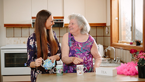 A lady and her carer enjoy conversation over cups of tea in a kitchen