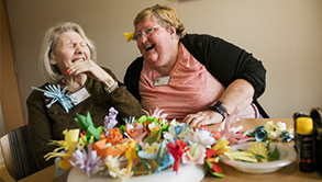 Two elderly ladies laughing in discussion whilst seated at a living room table