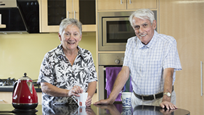 An elderly couple standing at a breakfast bar with their cups of tea.