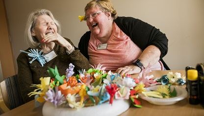 Elderly recipient of day and respite care enjoys a conversation with her carer